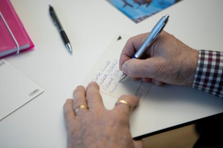 Mies kirjoittaa korttia.